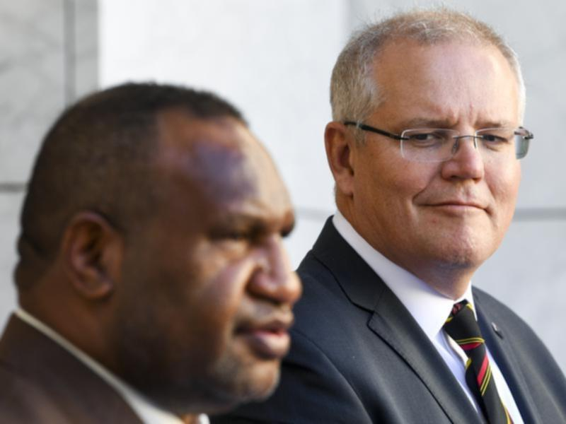 Scott Morrison listens during a joint statement with James Marape