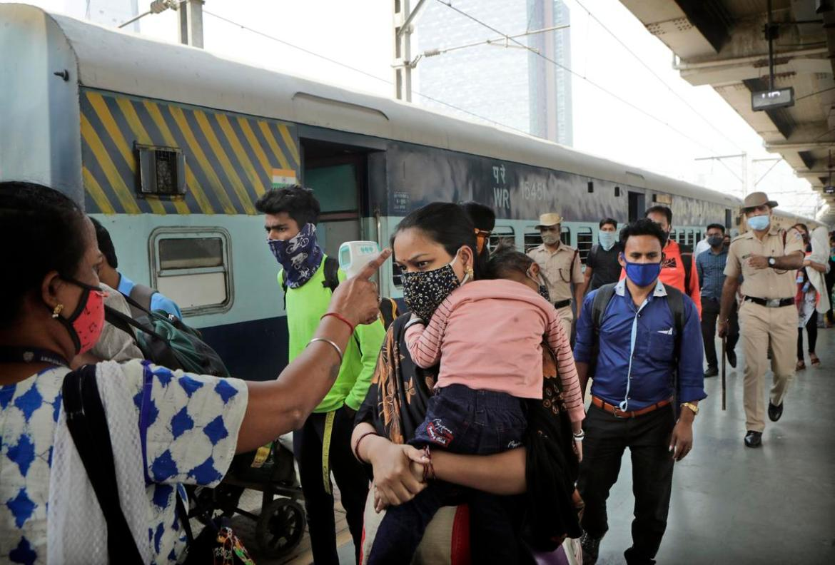 A health worker check temperature of a commuter at a train station in Mumbai, India, Thursday, Feb. 11, 2021.(AP Photo/Rajanish Kakade)