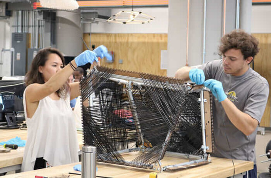 Members of the Ibañez Kim project team hand-weave carbon fiber strands at BUILD Space. Image Courtesy of Salem Chism