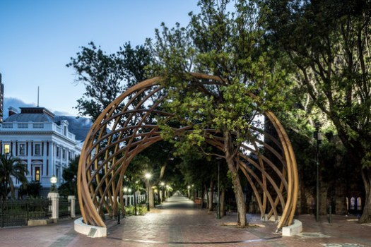 Sited between South Africa's National Parliament and St. George's Cathedral, the seat of the Archbishop of Cape Town, the Arch frames the public entrance to a landscaped promenade known as the Company's Garden, which boasts many of the city's cultural institutions. Image © David Southwood