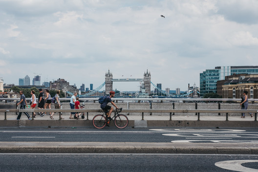 Cyclist and pedestrians on London Bridge, London, UK, River Thames and Tower Bridge on the background. Image via Shutterstock/ By Alena Veasey