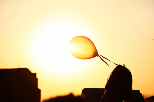girl joyful with balloon at sunset