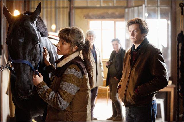 Raphaëlle (Lou De Lâage) s'occupe de Jappeloup, le cheval de Pierre Durand (Guillaume Canet) sous les yeux de Dalio (Jacques Higelin) et Serge Durand (Daniel Auteuil)