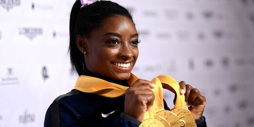 Simone Biles of The United States poses for photos with her multiple gold medals