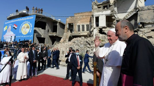Pope Francis (C), raises his hand in greeting as he arrives at a square near the ruins of the Syriac Catholic Church of the Immaculate Conception in northern Iraq