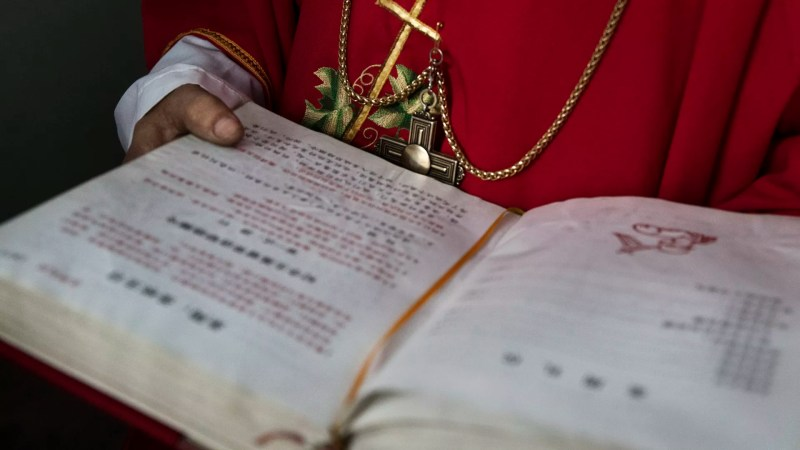 A Chinese Catholic deacon holds a bible at the Palm Sunday Mass during the Easter Holy Week at an 'underground' or 'unofficial' church