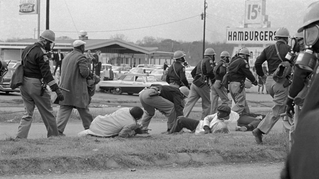 Historical photo of civil rights protesters in 1965 Selma, Alabama, injured on the ground and being ignored by passing police
