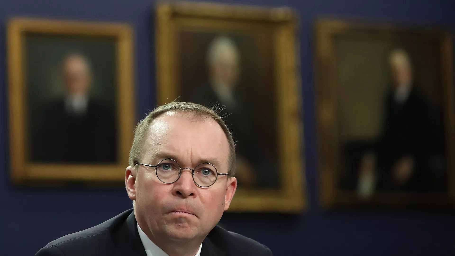Consumer Financial Protection Bureau  CFPB    Axios Mick Mulvaney looking straight at the camera with an unhappy look on his  face