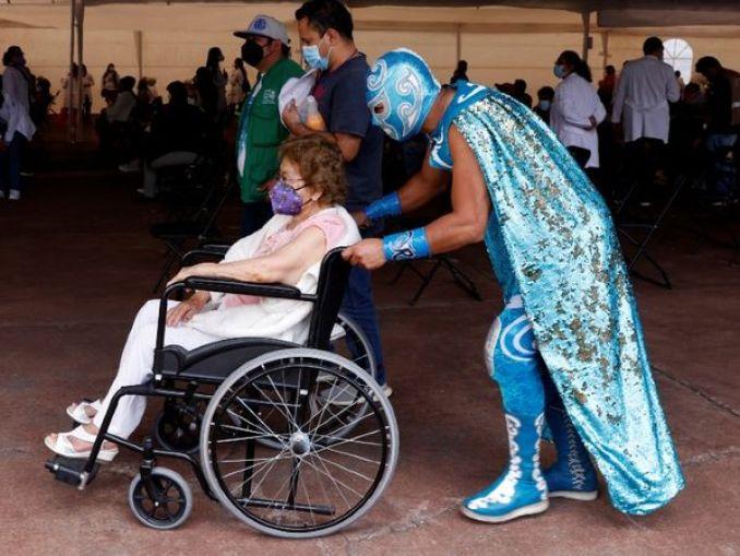 मैक्सिको की राजधानी मैक्सिको सिटी में एक बुजुर्ग महिला को वैक्सीन लगाने के प्रेरित करता रेसलर (WWE फाइटर)। - Dainik Bhaskar
