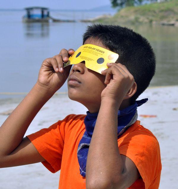 गुवाहाटी में सूर्यग्रहण का शानदार नजारा देखता एक बच्चा।