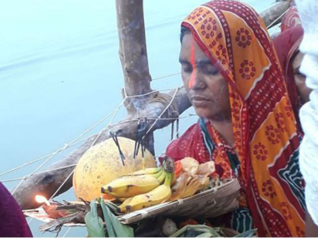 A woman decorated in the soup with tekua, fruit and quasar to offer the sixth maiya at a ghat in Patna.