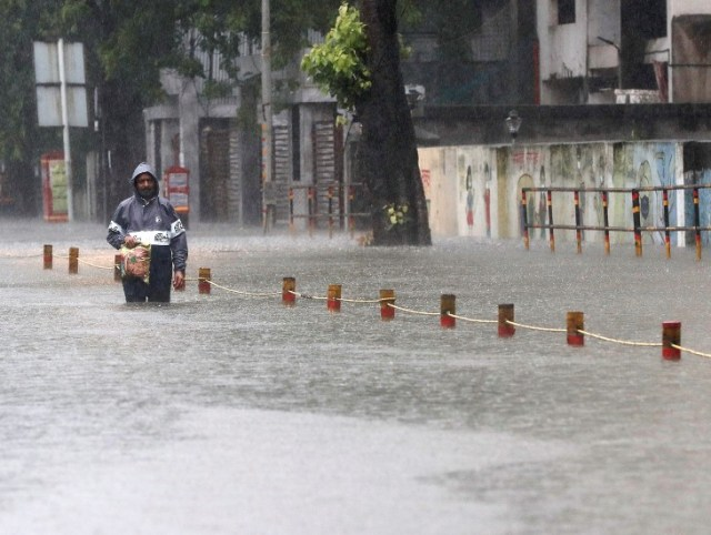 A man carrying goods from the market in Mumbai's Sion area amid heavy rains