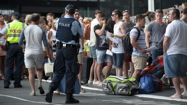 Police stand near school leavers attending the first day of Schoolies 2013 on the Gold Coast.