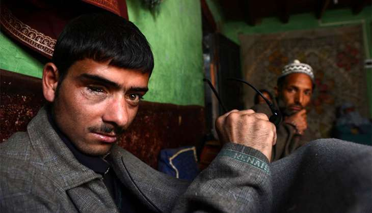 In this picturea taken on 22 March, 2013 eighteen year old Tariq Gojri (L) who lost his right eye to a  pellet gun allegedly fired by Indian police officials poses with family members during an interview with  AFP at his home in Khanpora.