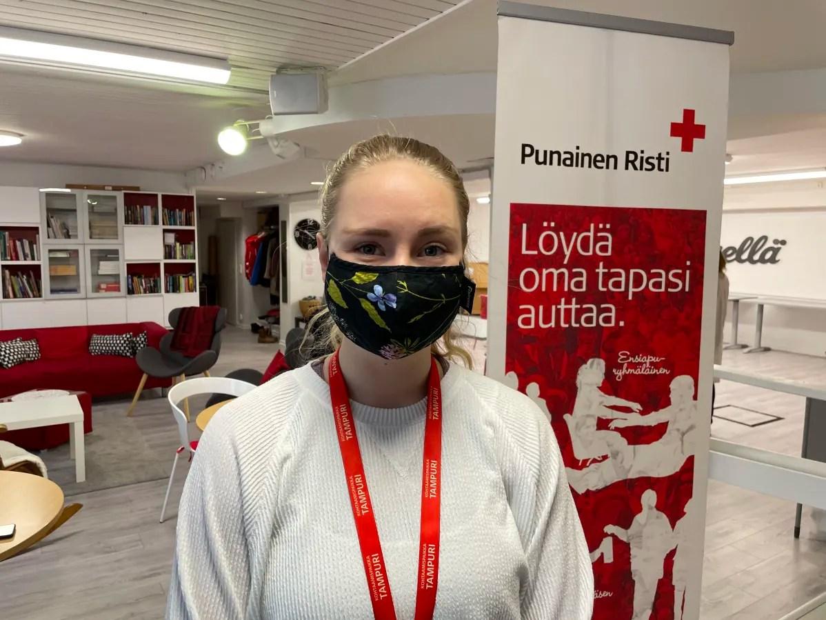 Nainen hymyilee maski kasvoillaan SPR:n Tampurin tiloissa Tampereella.