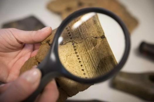 Nuorakeramiikan palanen tutkijan kädessä suurennuslasin läpi kuvattuna.