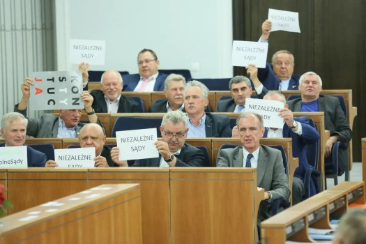 """Lakiehdotusta vastustavat senaattorit heiluttavat lappuja, joissa lukee """"itsenäinen oikeuslaitos"""" Puolan senaatissa 22. heinäkuuta 2017."""