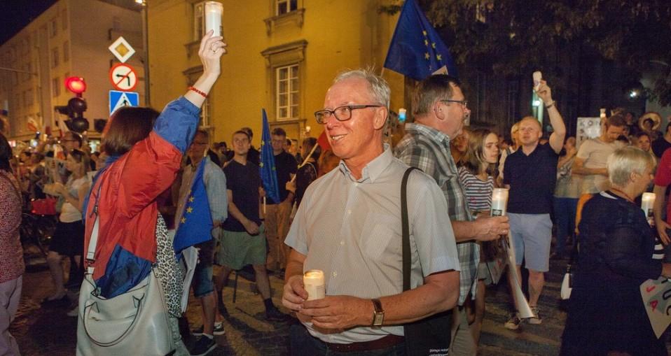 Mielenosoittajia iltahämärässä, käsissä kynttilöitä ja EU-lippuja.
