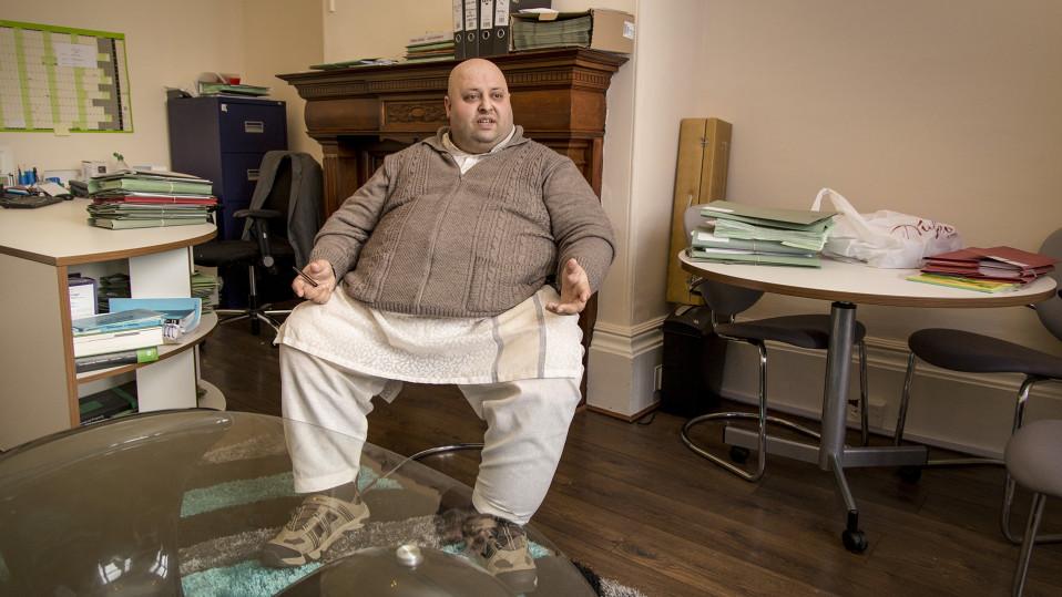Villatakkiin ja perinteiseen pakistanilaiseen housuasuun pukeutunut mies istuu keskellä toimistohuonetta.