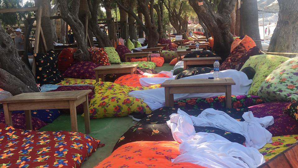 Paljon tyynyjä ja peittoja puiden alla lepopaikassa hotellin pihalla.