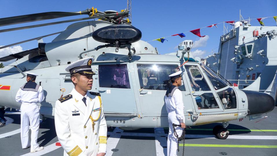 helikopteri ja kolme sotilasta laivan kannella