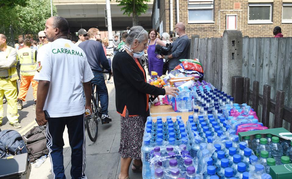 Ihmiset auttavat Grenfell Tower -kerrostalon asukkaita.