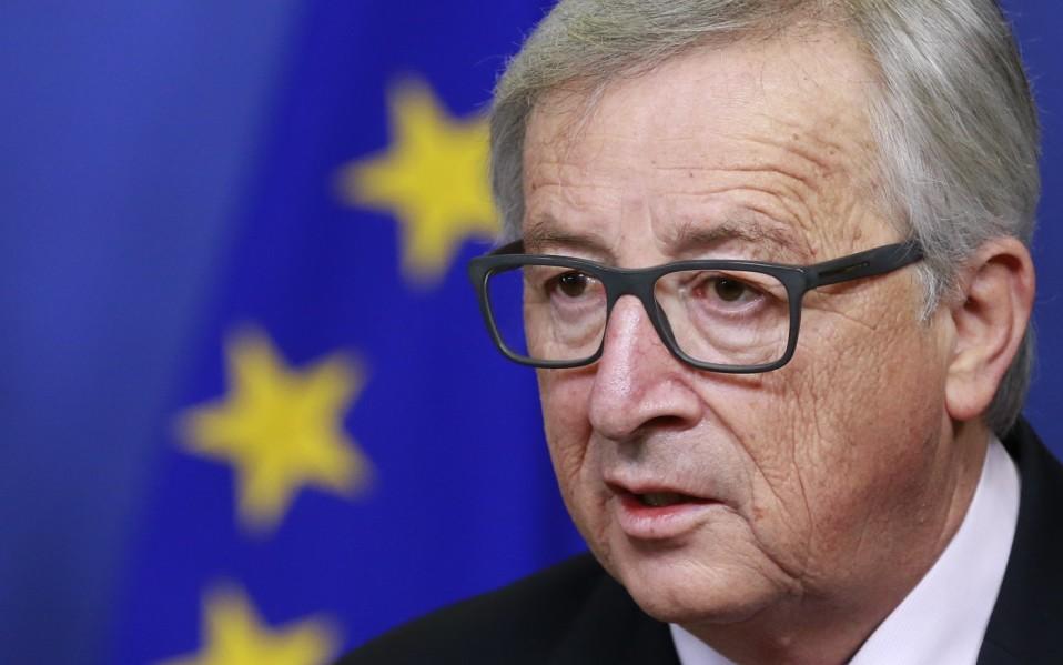 Silmälasipäinen mies taustalla näkyy EU:n lippua.