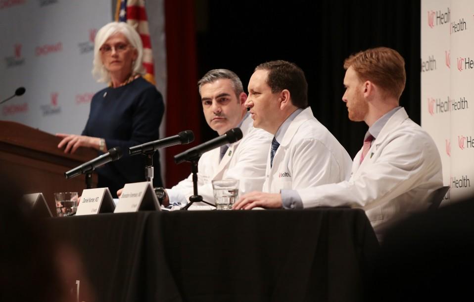 Etualalla kolme lääkäriä pöydän ääressä, takana nainen puhujapöntössä.