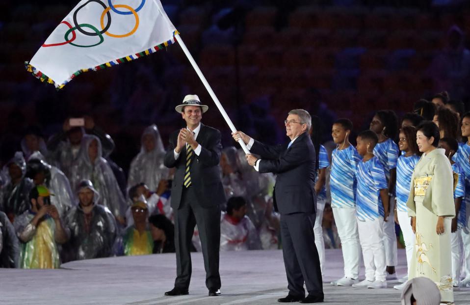 Rion entinen kaupunginjohtaja taputtaa lavalla, kun KOK:n presidentti Thomas Bach liehuttaa olympia-lippua Rion kesäolympialaisten päättäjäisissä. Lavalla on myös tuleva kisaisäntä Tokion kuvernööri Yuriko Koike.