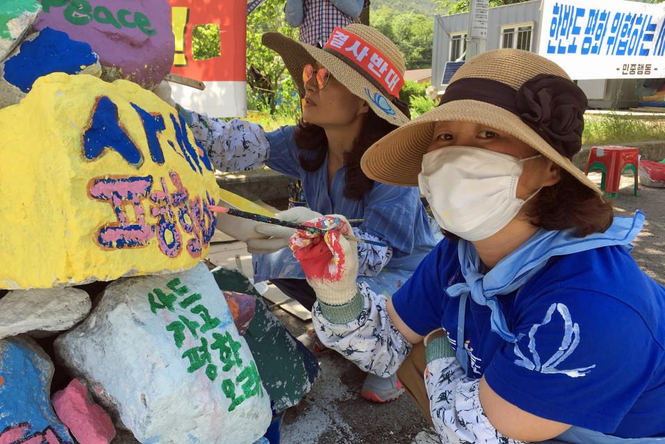 Torjuntaohjusten vastustajat maalaavat viestejään kiviin.