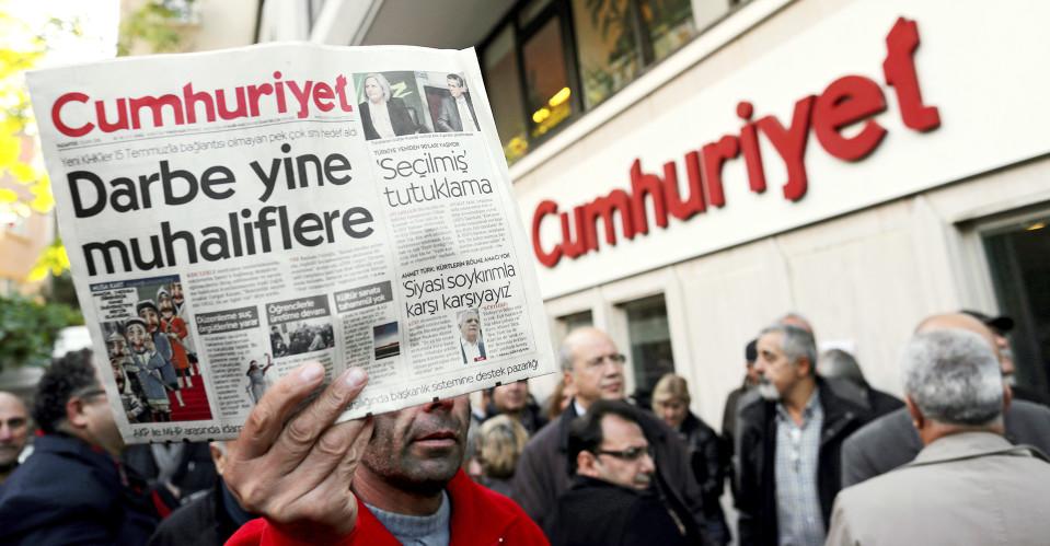 mies pitelee kädessään Cumhuriyet -sanomalehteä.