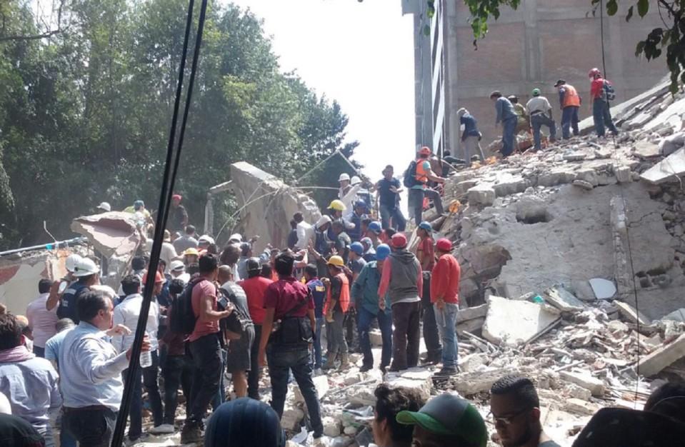 Ihmisiä rivissä romahtaneen rakennuksen vieressä ja päällä