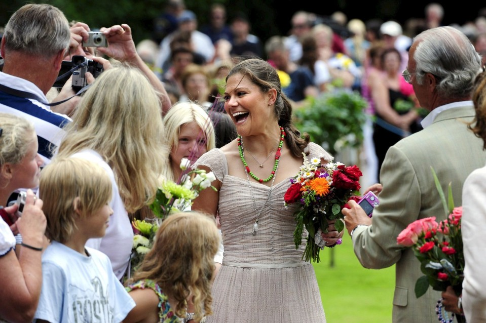 Hymyilevä Victoria ihmisten ympäröimänä, pitää kädessään kukkakimppua.