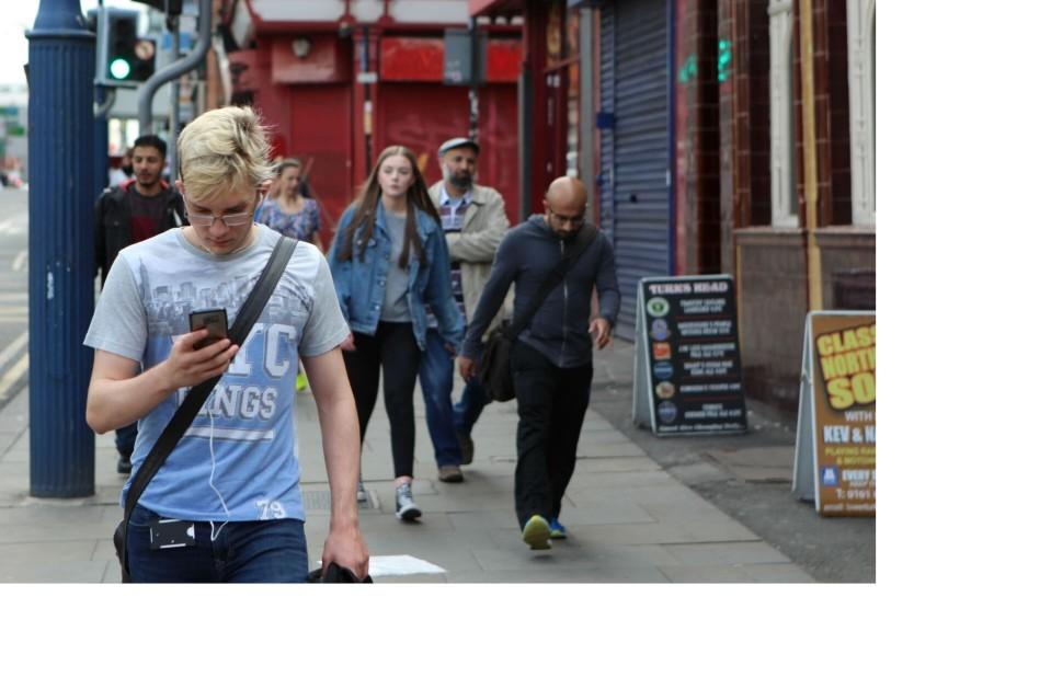 Ihmisiä kadulla. Nuori mies selaa kännykkäänsä, taustalla viisi muuta ihmistä.