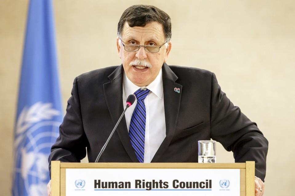 Sarraj seisoo puhujanpöntön takana ja puhuu mikrofoniin. Hänellä on tumma puku ja siniraitainen kravatti. Sarrajilla on harmaat viikset, tumma tukka ja silmälasit. Taustalla näkyy YK:n sininen lippu.