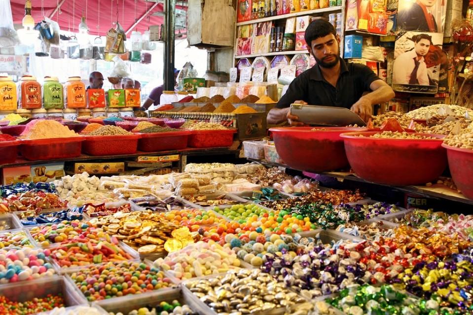 Kuvassa makeisia ja mausteita kaupassa Irakin Bagdadissa. Myyjä annostelemassa myytävää.