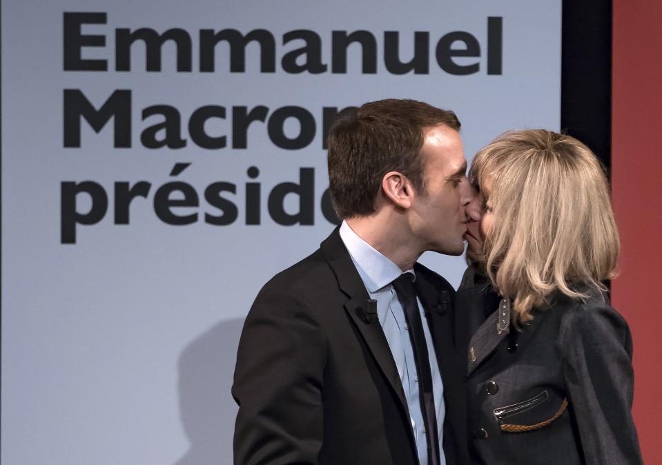 Brigitte Trogneux ja Emmanuel Macron suutelevat.