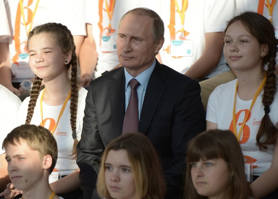 Vladimir Putin istumassa kahden lettipäisen tytön välissä.