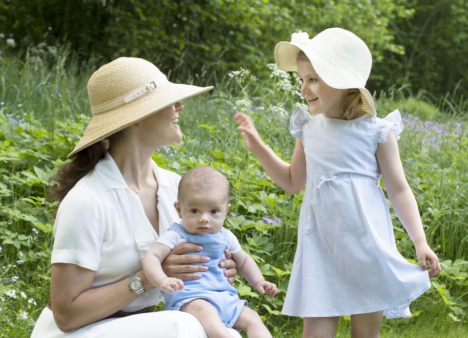 Kruununprinsessa Victoria, prinssi Oscar ja prinsessa Estelle puutarhassa.