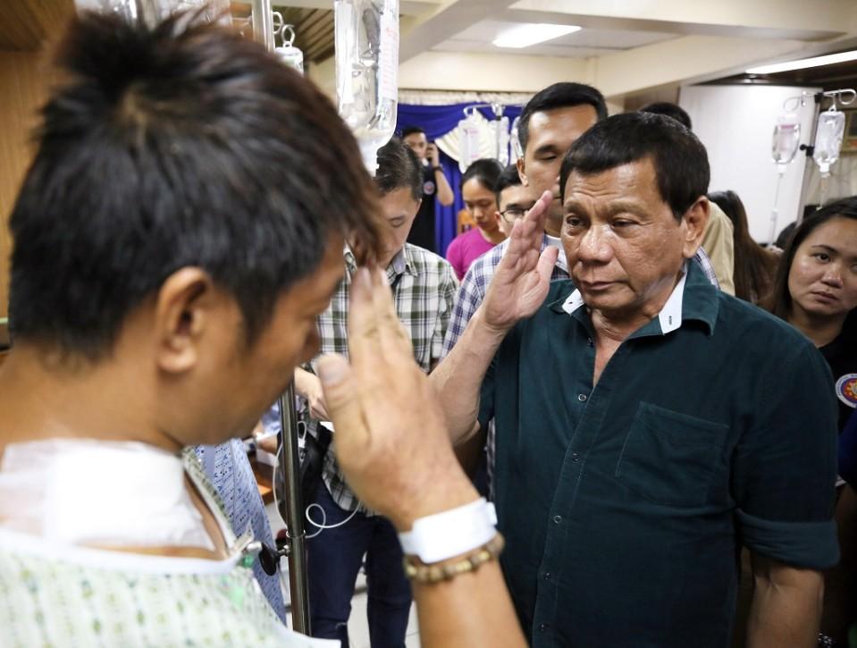 Duterte tekee kunniaa sotilaalle, joka on sairaalan vaatteissa.