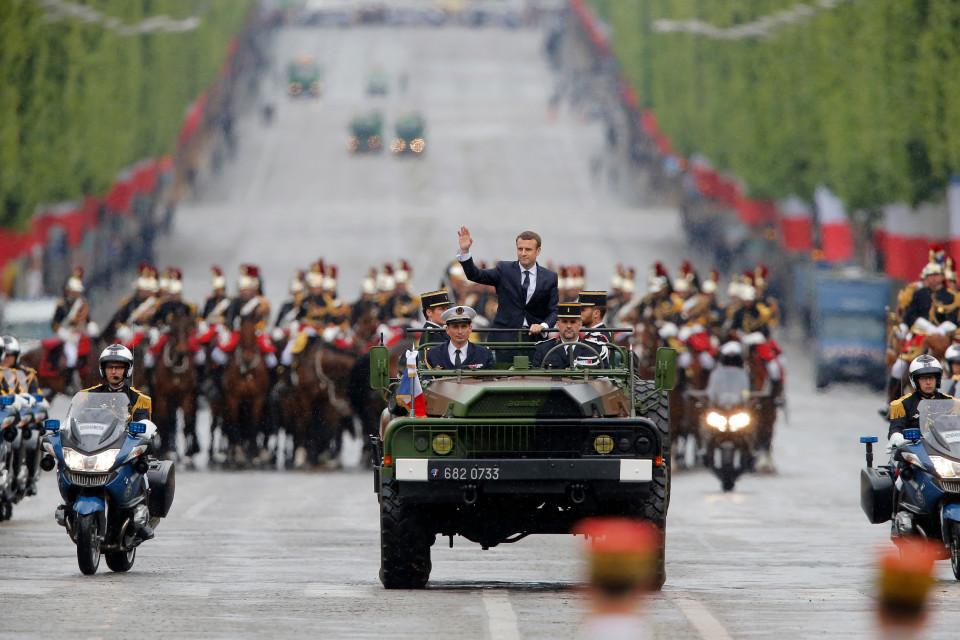 Macron vilkuttaa autossa Champs-Elysees'llä.