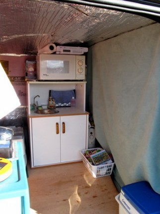 Looking forward we can see the heavy, insulated curtain Sarah hung between the living area and the front driving area. This is extremely important in cold country but is also a requirement for stealth and privacy.