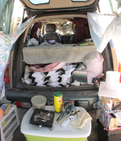 The PT Cruiser from the back. The shelf was part of the car and she slept with her feet under it.  You can see it was a very comfortable home. However, I saw the wind flatten it literally dozens of times. The owner of this car is one tough lady because she always just rebuilt it and gathered her stuff from around the desert and kept on keeping-on. The universe rewarded her by providing a really great high-top conversion van in great shape for $1200!! And she had earned it!