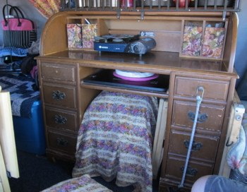 """Cheri found this very nice but well-used roll-top desk at a thrift store for just a few dollars. All the furniture in the van is bolted to the floor with """"L"""" brackets."""