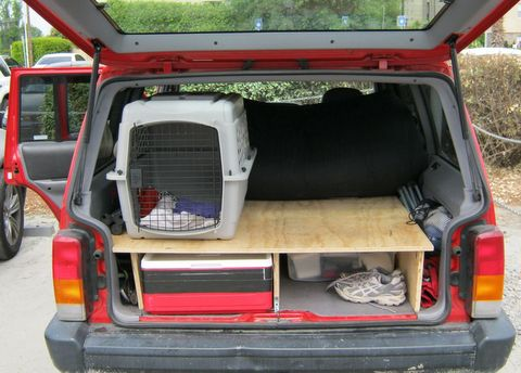 """A view of the back of the Cherokee in """"day position."""" Sprocket quickly refused to ride in his crate preferring the freedom of the whole back of the rig. Our bedding folded under the mattress vaguely protecting it from puppy hair. When he was wet or sandy he went into his crate. You can also see our stackable cooler that we cut the handles off to fit into the available space."""
