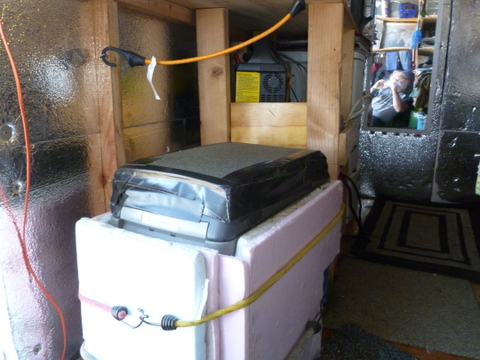 I have a 12 volt compressor cooler/freezer made by Dometic/Waeco. It is on the floor under the counter-top toward the front by the door. There can't be any legs up front since the lid is hinged on one end and I need to be able to get into it.