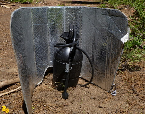Here is a pump-up garden sprayer painted black to get hot in the sun. Makes a great shower!