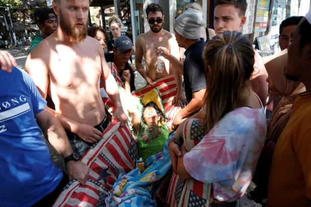 Turistas ayudan a una mujer herida. (EFE)