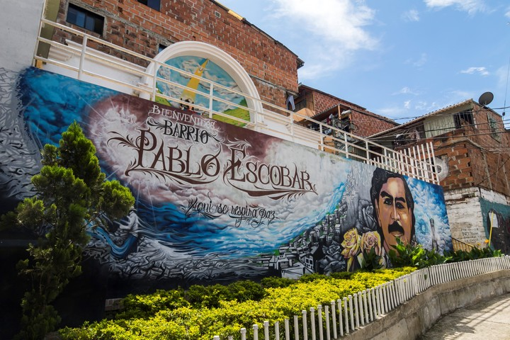 """21 November 2018, Colombia, Medellin: A gigantic and colorful mural with the face of """"The boss"""" and the legend """"Welcome to the Pablo Escobar neighborhood"""" presides over the entrance to the neighborhood """"Pablo Escobar"""".  Photo: Daniel Romero / dpa"""