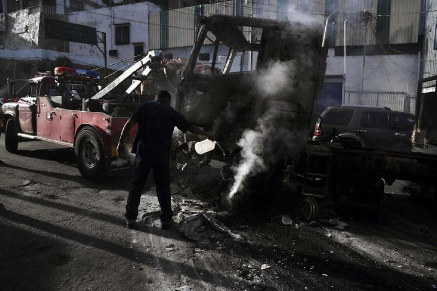 Un hombre trata de apagar el fuego en un camión incendiado durante disturbios en las protestas. (AFP)